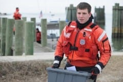 Petty Officer 2nd Class Adam Preiser, a boatswain mate at Coast Guard Station Hatteras Inlet, carries a box of medicine and pharmaceutical supplies off the ferry pier on Ocracoke Island.