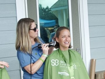 Shaving Marilyn Savage's head. Savage was the largest single fundraiser, bringing $1663 to the Outer Banks Shave Riders.