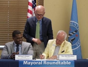 Dare County Board Chair Bob Woodard provides final signature to resolution opposing offshore drilling for oil or gas. NCDEQ Secretary Michael Regan, Mayor Ben Cahoon, Bob Woodard.